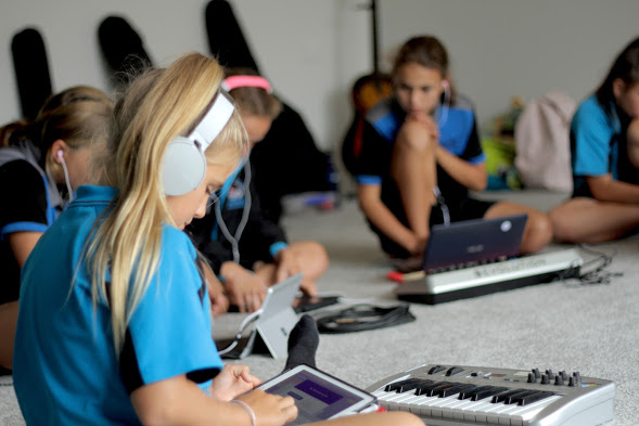 A group of kids learning to write music